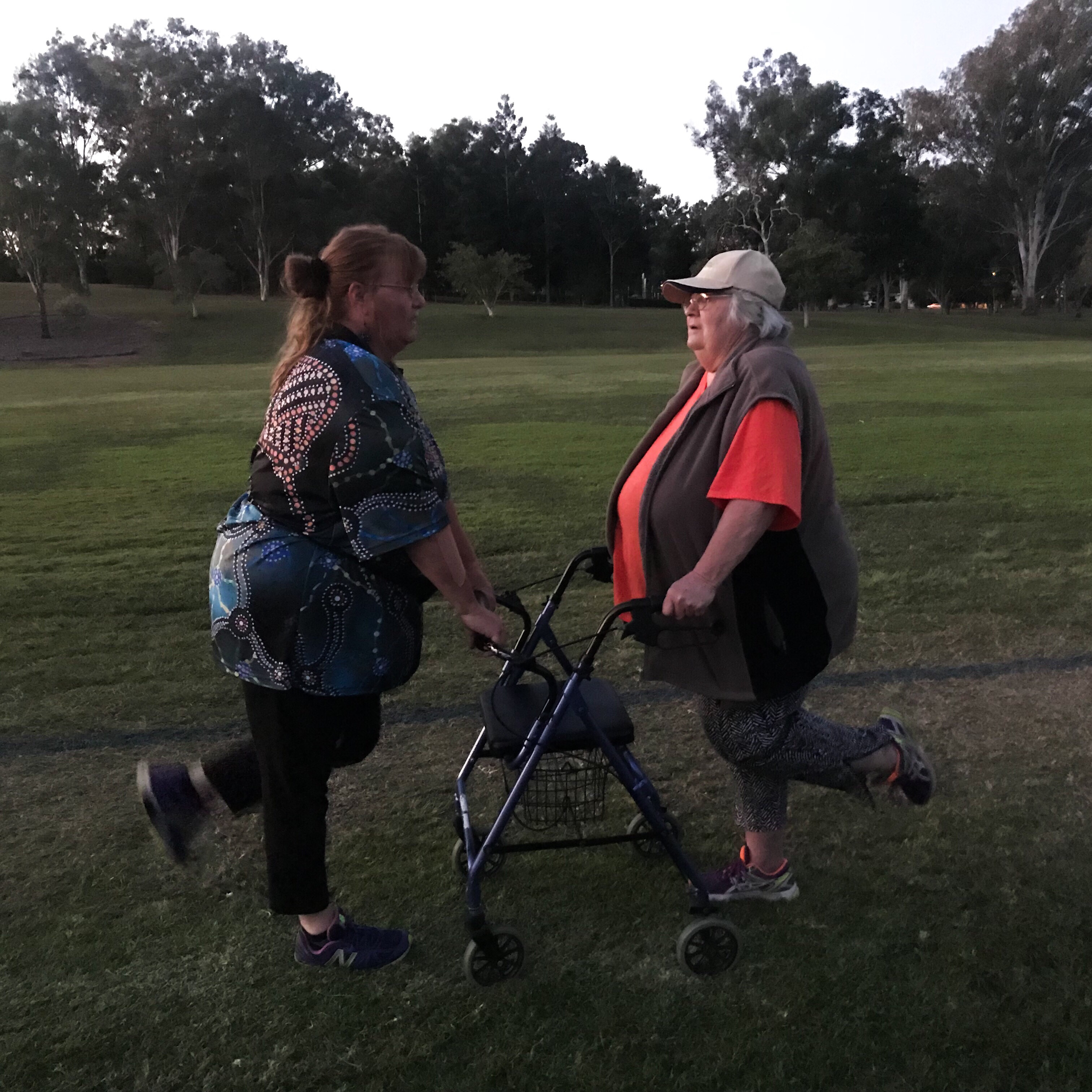 On a green oval, two women wearing exercise gear face each other, holding onto the older woman's walker, one leg each raised behind them.