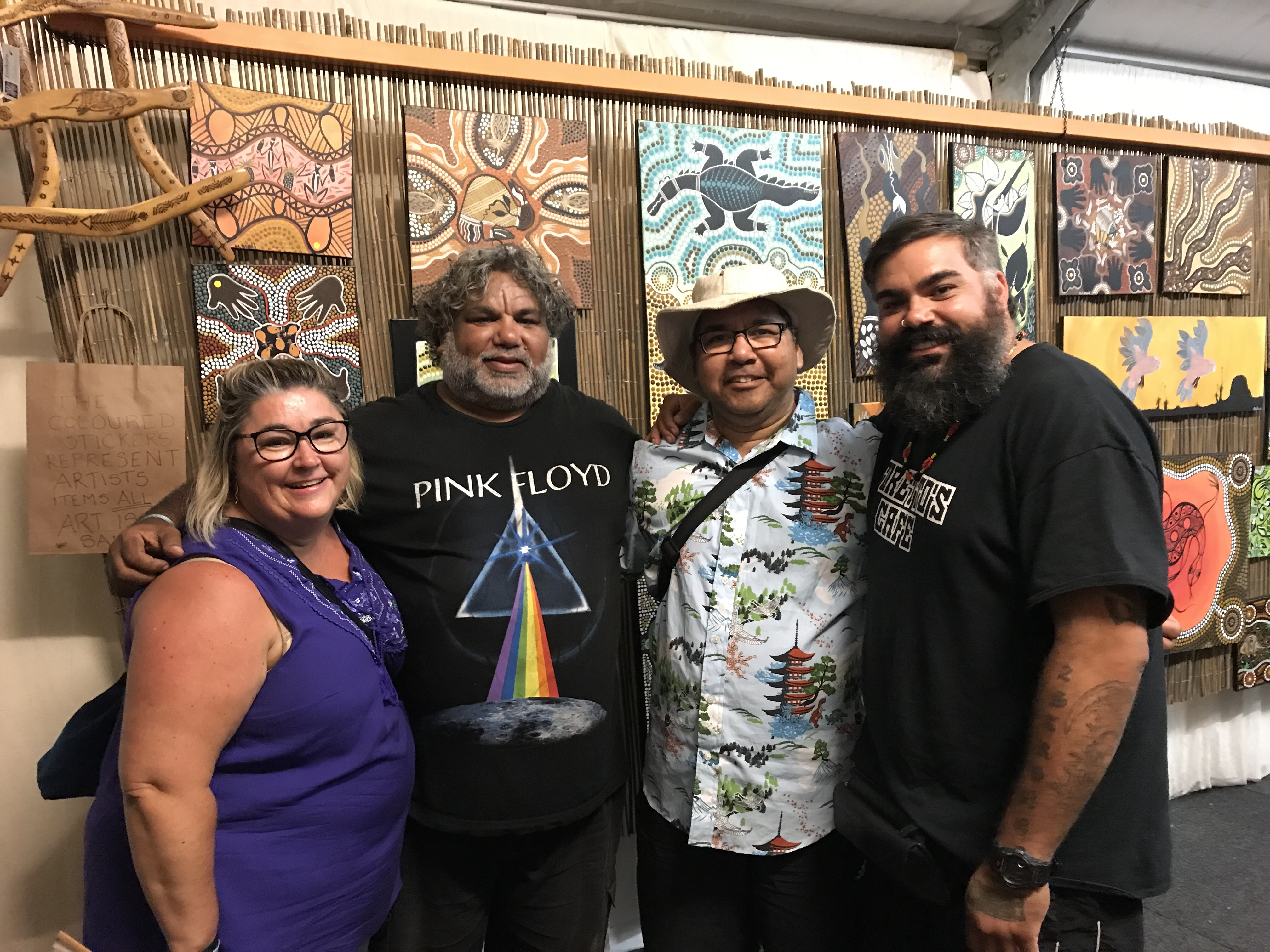 Four people stand smiling at the camera, behind them Aboriginal paintings hang in the background.